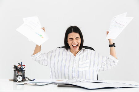 Photo for Photo of nervous brunette businesswoman 30s screaming and stressing while working with paper documents in office isolated over white background - Royalty Free Image