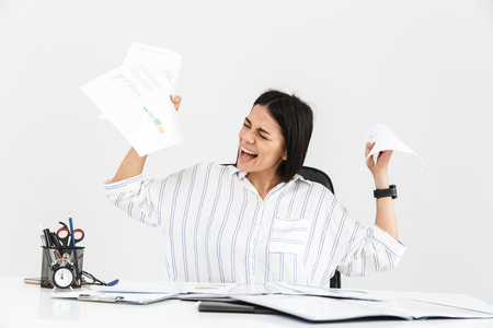 Photo for Photo of confused brunette businesswoman 30s screaming and stressing while working with paper documents in office isolated over white background - Royalty Free Image