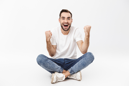 Foto de Full length of a cheerful young man sitting with legs crossed isolated over white background, celebrating success - Imagen libre de derechos