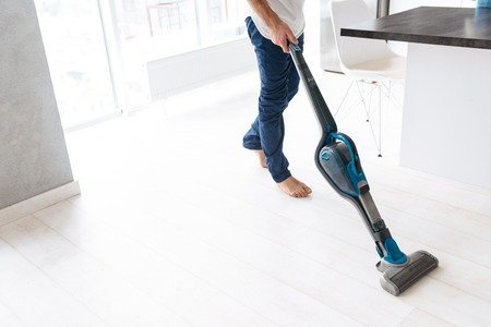 Photo pour Close up of a man vacuuming the floor at the kitchen - image libre de droit