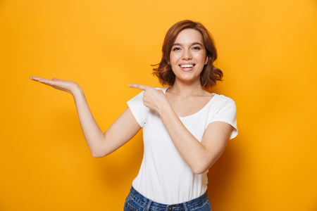 Foto de Cheerful young girl wearing t-shirt standing isolated over yellow background, presenting copy space - Imagen libre de derechos