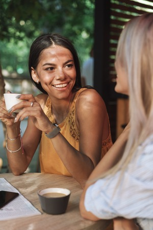 Photo for Two cheerful young girlfriends sitting at the cafe table indoors, talking - Royalty Free Image