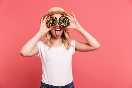 Photo for Portrait of pretty blond woman 20s wearing straw hat laughing while holding tasty sweet donuts isolated over pink background - Royalty Free Image