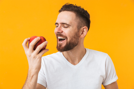 Photo for Photo of a happy young handsome man posing isolated over yellow wall background holding apple. - Royalty Free Image
