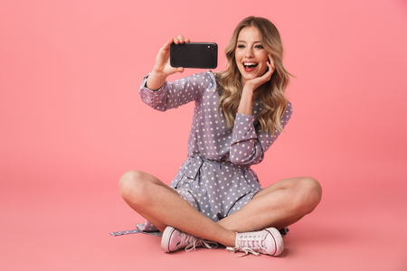 Foto de Portrait of a cheerful young blonde girl sitting on a floor isolated over pink background, taking a selfie - Imagen libre de derechos