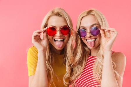 Photo pour Funny blonde twins in sunglasses having fun while showing their tongues and looking at the camera over pink background - image libre de droit