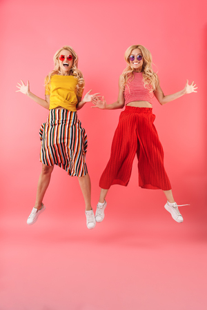 Photo pour Full length image of Happy blonde twins in sunglasses jumping and looking at the camera over pink background - image libre de droit