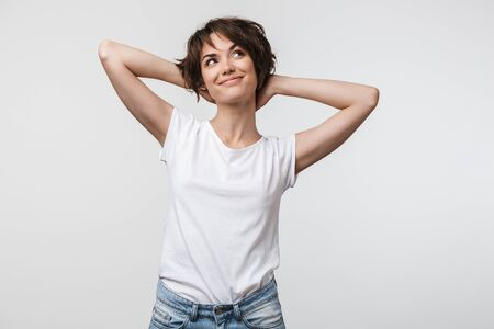 Photo for Image of optimistic woman in basic t-shirt touching her hair and looking aside isolated over white background - Royalty Free Image