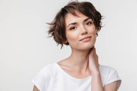 Foto de Portrait of pretty woman with short brown hair in basic t-shirt looking at camera while standing isolated over white background - Imagen libre de derechos