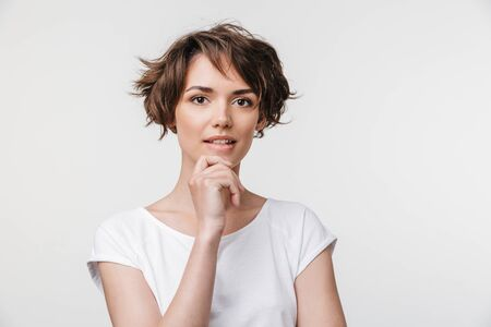 Photo for Portrait of attractive woman with short brown hair in basic t-shirt looking at camera while standing isolated over white background - Royalty Free Image