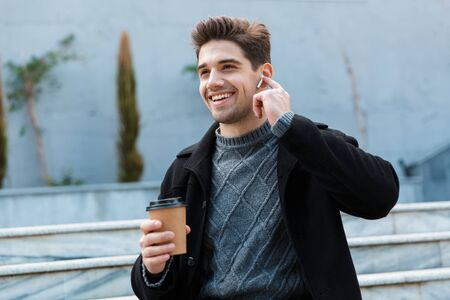 Foto de Image of happy man 30s wearing earpods smiling and drinking takeaway coffee while sitting on city stairs - Imagen libre de derechos