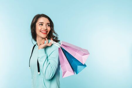 Foto für Portrait of a beautiful excited young brunette woman standing isolated over blue background, carrying shopping bags - Lizenzfreies Bild