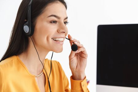 Foto de Photo of beautiful phone operator woman wearing microphone headset sitting at her workplace in office and speaking with client - Imagen libre de derechos