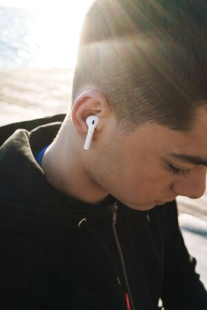 Foto per Photo of young sportsman 20s in tracksuit wearing earpods walking by seaside in the morning while doing sports - Immagine Royalty Free