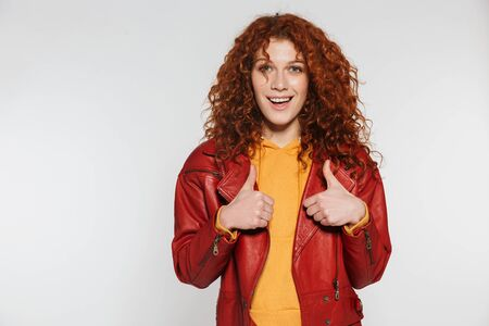 Foto de Portrait of an attractive redhead young woman standing isolated, showing thumbs up - Imagen libre de derechos