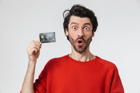 Foto de Image of a handsome young shocked man posing isolated over white wall background holding credit card. - Imagen libre de derechos