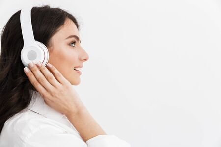 Photo for Close up side view of a beautiful young woman with long curly brunette hair wearing white shirt standing isolated over white background, enjoying listening to music with headphones - Royalty Free Image