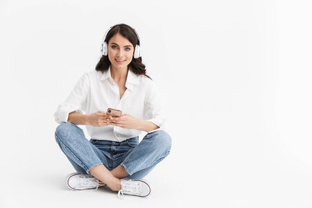 Photo for Cheerful young brunette woman wearing shirt sitting isolated over white background, listening to music with earphones and mobile phone - Royalty Free Image