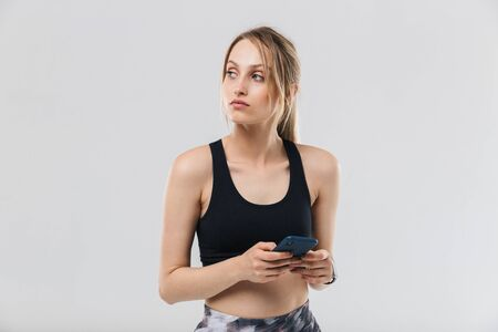Foto per Image of pretty blond woman 20s dressed in sportswear using smartphone during workout in gym isolated over white wall - Immagine Royalty Free