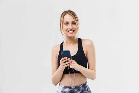 Foto per Image of beautiful blond woman 20s dressed in sportswear working out and listening to music with smartphone during fitness in gym isolated over white wall - Immagine Royalty Free