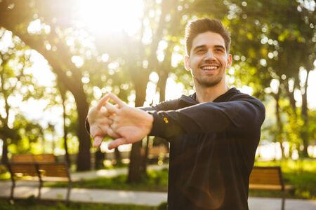 Photo pour Image of a handsome smiling young sports fitness man standing in green park nature make stretching exercises for arms. - image libre de droit