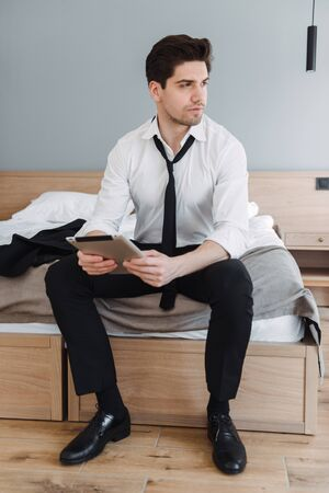 Photo pour Photo of handsome brooding businessman wearing formal clothes using tablet computer while sitting on bed in hotel apartment - image libre de droit