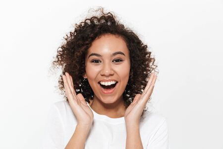 Foto de Portrait of a pretty cheerful casual african girl standing isolated over white background, celebrating success - Imagen libre de derechos