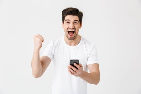 Foto de Image of excited happy young man posing isolated over white wall background using mobile phone make winner gesture. - Imagen libre de derechos