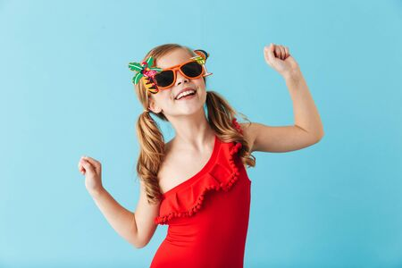 Foto de Cheerful little girl wearing swimsuit standing isolated over blue background, posing in sunglasses - Imagen libre de derechos