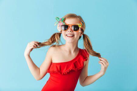 Foto de Cheerful little girl wearing swimsuit standing isolated over blue background, posing in sunglasses - Imagen libre de derechos
