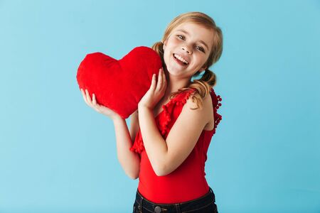 Foto de Cheerful little girl wearing swimsuit standing isolated over blue background, holding red heart - Imagen libre de derechos