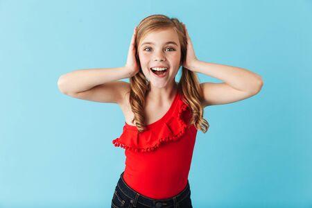 Foto de Cheerful little girl wearing swimsuit standing isolated over blue background, posing - Imagen libre de derechos