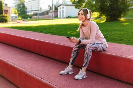 Foto per Image of a beautiful young fitness sports woman posing outdoors in park listening music with earphones using mobile phone. - Immagine Royalty Free