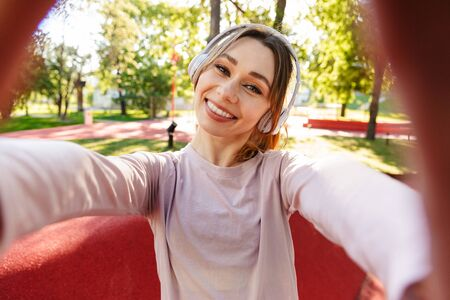 Foto per Image of a beautiful cheerful young fitness sports woman posing outdoors in park listening music with earphones take selfie by camera. - Immagine Royalty Free