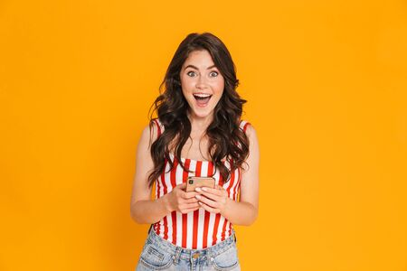Foto de Portrait of excited happy woman in striped t-shirt typing on smartphone and looking at camera isolated over yellow background - Imagen libre de derechos