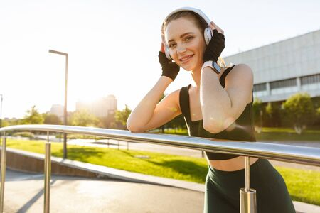 Foto per Image of feminine fitness woman 20s wearing tracksuit leaning on railing and listening to music with headphones while walking through green park - Immagine Royalty Free