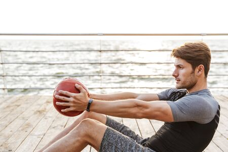 Photo pour Photo of caucasian man in tracksuit doing exercise with red fitness ball while working out on wooden pier at seaside in morning - image libre de droit