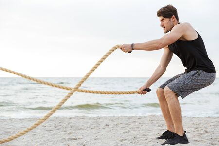 Photo pour Photo of strong young man in tracksuit working out with fitness rope on beach at seaside in morning - image libre de droit