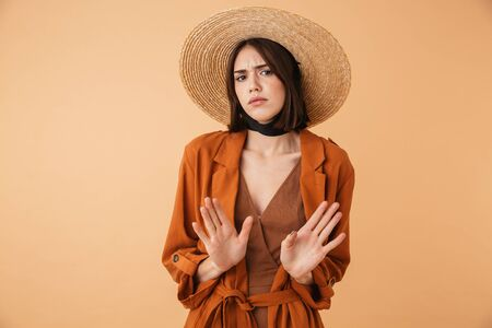 Foto de Beautiful confused young woman wearing straw hat standing isolated over beige background, arms outstretched - Imagen libre de derechos