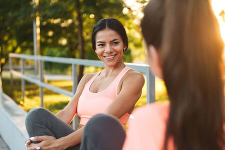 Photo pour Image of happy fitness women in sportswear smiling and talking together while sitting in green park - image libre de droit