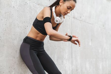 Foto per Attractive young fitness girl leaning on a wall while standing outdoors, resting after workout, looking at smart watch - Immagine Royalty Free