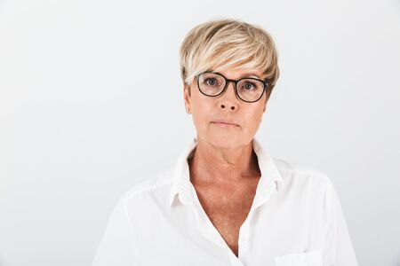 Foto de Portrait of caucasian adult woman wearing eyeglasses looking at camera isolated over white background in studio - Imagen libre de derechos