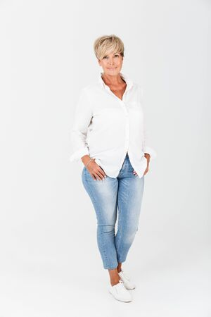 Foto de Full length portrait closeup of middle-aged woman with short blond hair looking at camera isolated over white background in studio - Imagen libre de derechos