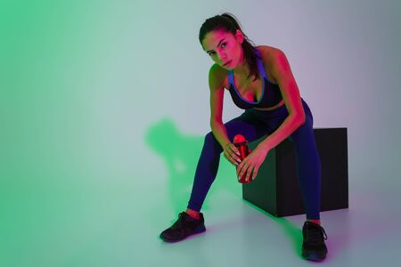 Photo for Photo of serious young fitness woman posing isolated with led flash lights holding bottle with water have a rest. - Royalty Free Image