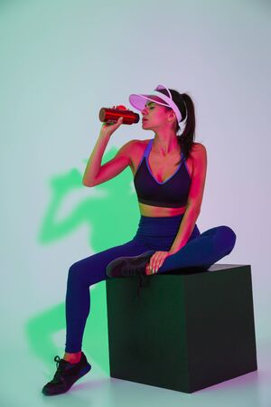 Photo for Image of gorgeous pretty young sports woman posing isolated with led flash lights in cap drinking water. - Royalty Free Image