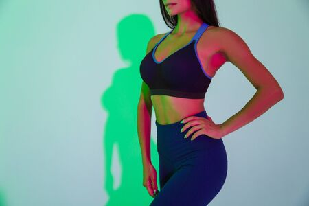 Photo for Cropped image of young sports woman posing isolated with led flash lights. - Royalty Free Image