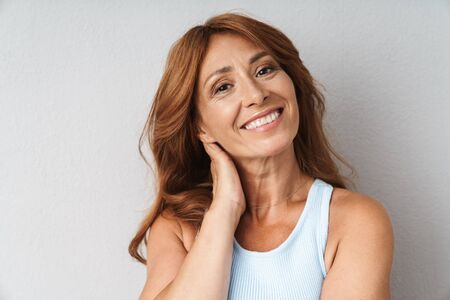 Photo for Portrait of an attractive smiling middle aged woman wearing casual outfit standing isolated over beige background, looking at camera - Royalty Free Image