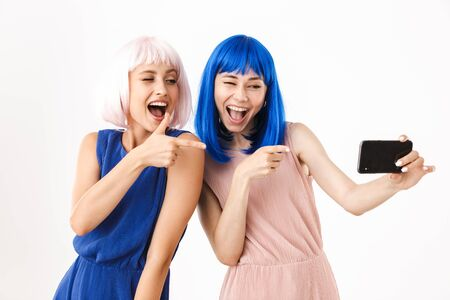 Foto de Portrait of two funny women wearing blue and pink wigs taking selfie photo and pointing fingers at cellphone isolated over white background - Imagen libre de derechos