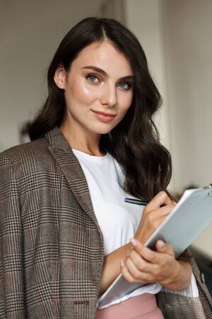Attractive smiling young businesswoman standing at the office, holding notepad