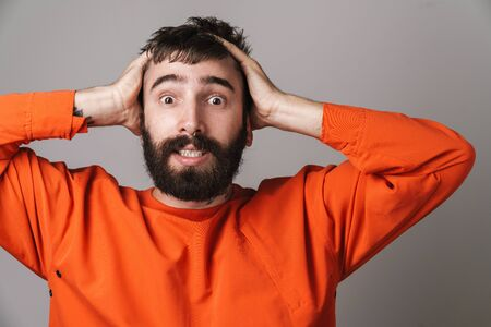 Photo for Image of young bearded man with nose jewelry wearing orange shirt stressing and grabbing his head isolated over gray background - Royalty Free Image